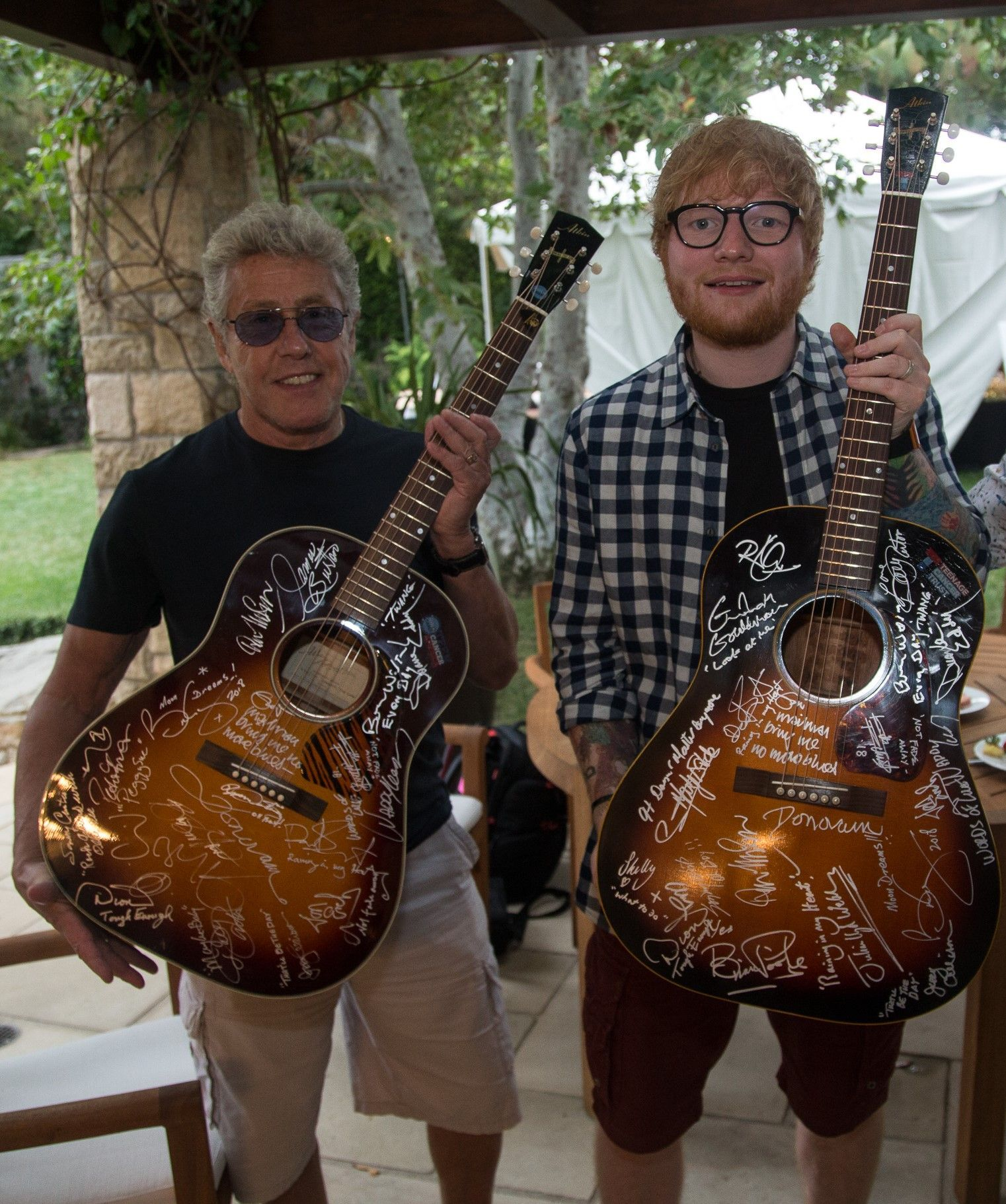 Roger Daltrey and Ed Sheeran holding signed Buddy Holly guitars